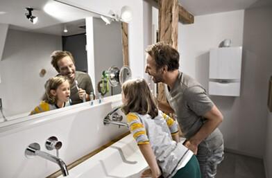 Novi bojler – otac i sin peru zube u kupaonici s kondenzacijskim bojlerom u pozadini